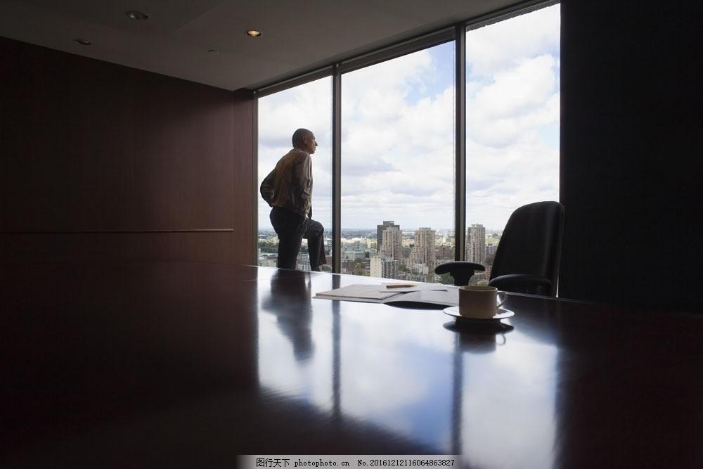 站在窗户看风景的商务男人图片